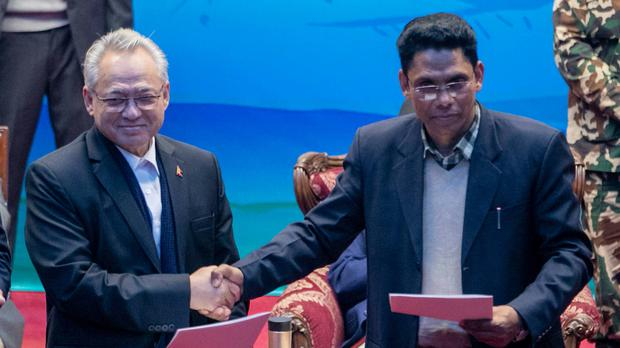 Nepalese Home Minister Ram Bahadur Thapa, left, and the spokesperson of the Nepal Communist Party group Khadga Bahadur Bishwakarma shake hands during a signing of peace agreement in Kathmandu, Nepal, Friday, March 5, 2021. The leader of the small rebel group Netra Bikram Chand , who is better known by his guerrilla name Biplav, merged out of hiding on Friday after the government lifted a ban on his group so it could take part in the public signing of the peace agreement. This group had split from the Maoist Communist party, which fought government troops between 1996 and 2006, when it gave up its armed revolt, agreed to U.N.-monitored peace talks and joined mainstream politics. (AP Photo/Niranjan Shrestha)
