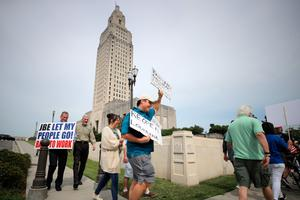 Protesters gather outside the Louisiana State Capitol during a rally against Louisiana's stay-at-home order and economic shutdown