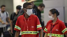 Staff wear masks as a precaution against the spread of coronavirus at Sao Paulo International Airport in Brazil (Andre Penner/AP)