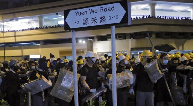 Protesters with protection gear hold home-made shield as they prepare to face off with policemen in Sha Tin District in Hong Kong (Kin Cheung/AP)