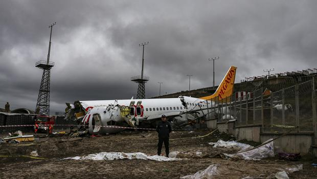 Turkish police guard the wreckage of a plane after it skidded off the runway at Istanbul's Sabiha Gokcen Airport (Emrah Gurel/AP)