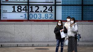 Women stand in front of at an electronic stock board showing Japan's Nikkei 225 index at a securities firm in Tokyo on Thursday, as Asian markets dived (Eugene Hoshiko/AP)