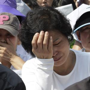 Workers weep during a May Day rally to pay tribute to the victims of the sunken ferry Sewol in Seoul, South Korea (AP)