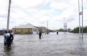 People wade through a flooded street in Somalia (AP)