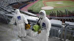 Workers wearing protective gear disinfect as a precaution against the new coronavirus at Gocheok Sky Dome in Seoul on Tuesday. South Korea's baseball season is one of the countless events and institutions affected by the coronavirus (Lee Jin-man/AP)