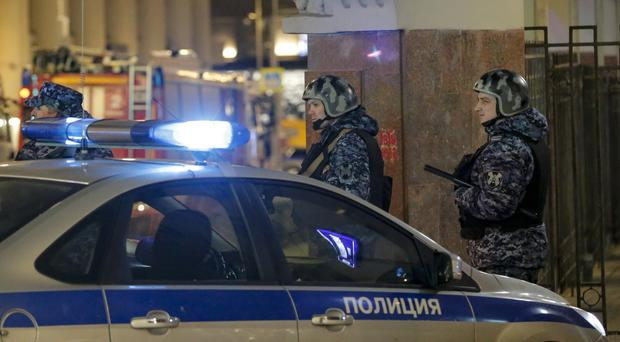 Russian police officers secure the area near the building of the Federal Security Service (FSB, Soviet KGB successor) in the background in Moscow, Russia, Thursday, Dec. 19, 2019. Russian officials say an officer of Russia's main security agency has been killed by an unidentified gunman near its Moscow headquarters and five others have been injured. (AP Photo/Alexander Zemlianichenko Jr)