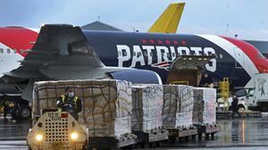 Palettes of N95 respirator masks are off-loaded from the New England Patriots NFL team's customised Boeing 767 jet in Boston. US states are growing more creative in accessing protective equipment outside of normal channels as the coronavirus crisis deepens (Jim Davis/AP)
