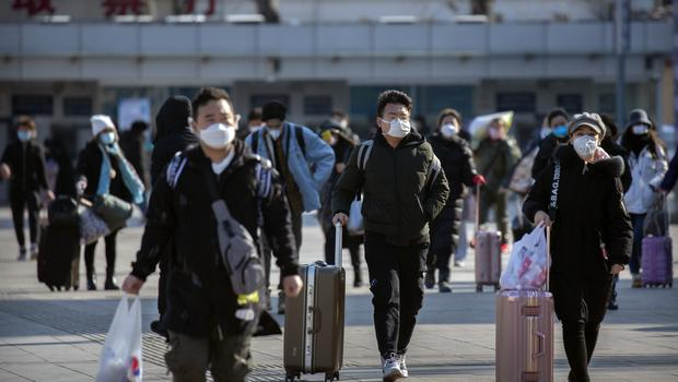 Travellers wear face masks outside Beijing railway station as people returning to the city will now have to isolate themselves either at home or in a concentrated area for medical observation (Mark Schiefelbein/AP)