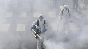 Firefighters disinfect a street against the new coronavirus, in western Tehran (AP)
