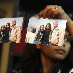 Relatives hold up pictures of passengers missing on the Malaysia Airlines flight (AP)
