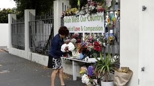 A woman prepares to place flowers at the Al Noor mosque in Christchurch, New Zealand (Mark Baker/AP)