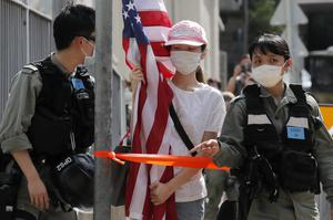 A protester carrying an American flag outside the US consulate in Hong Kong (AP)