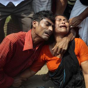 Relatives mourn a victim at the site where an eight-storey building housing several garment factories collapsed in Savar, near Dhaka, Bangladesh (AP)
