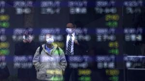 People are reflected on an electronic stock board showing Japan's Nikkei 225 index at a securities firm in Tokyo on Friday (Eugene Hoshiko/AP)
