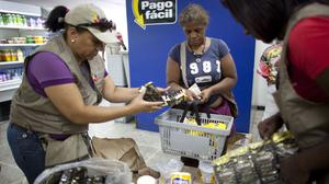 A government worker hands coffee to a shopper inside a Dia a Dia supermarket in Caracas (AP)