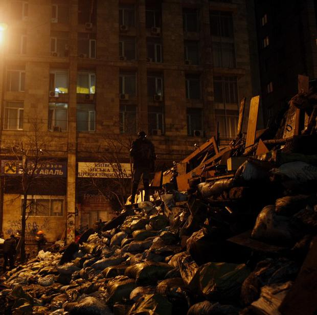 An anti-government protester stands on a barricade at Independence Square in Kiev (AP)