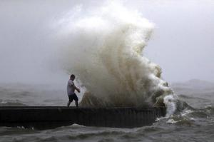 A wave crashes as a man stands on a jetty near Orleans Harbour in Lake Pontchartrain in New Orleans (Gerald Herbert/AP)