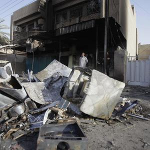 A man inspects the aftermath of a car bomb attack in the neighborhood of Shaab in Baghdad (AP)