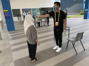 A voter wearing a face mask has her temperature checked with a thermal scanner (Royston Chan/AP)
