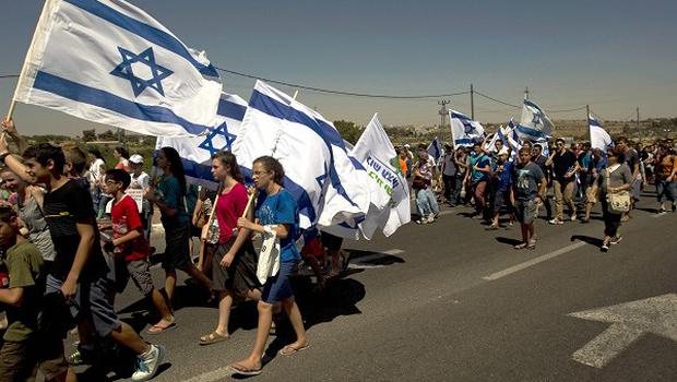 Israelis march on the road near where three Israeli teenagers were abducted near the West Bank Jewish settlement of Alon Shvut (AP)