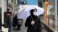 A pedestrian wears a mask and gloves to help guard against the Coronavirus, in downtown Tehran, Iran (Ebrahim Noroozi/AP)