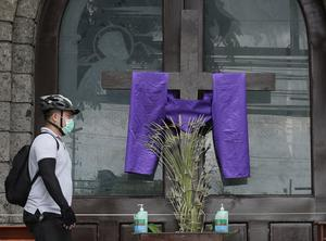 A crucifix in front of the closed doors of St Peter's parish church in Manila (Aaron Favila/AP)