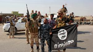 Shiite militiamen hold the flag of the Islamic State militant group they captured during an operation north of Baghdad. (AP)