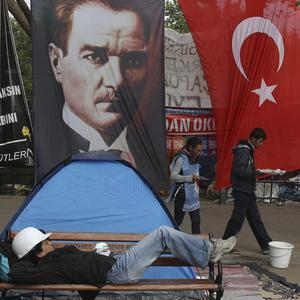 A protester relaxes on a bench next to a portrait of Mustafa Kamal Ataturk, founder of the modern Turkey, at Gezi Park, Taksim Square (AP)