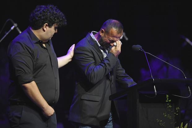 Temel Atacocugu, right, who survived being shot nine times during the attack on the Al Noor mosque, cries as he speaks at a remembrance service (Kai Schwoerer/Pool via AP)