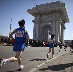 Runners pass the Arch of Triumph in Pyongyang in last year's Mangyongdae Prize Marathon (AP)