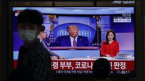 Someone in a face mask walks past an image of Donald Trump on TV in Seoul, South Korea (AP)