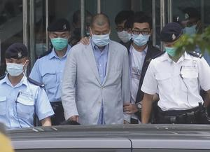 Hong Kong media tycoon Jimmy Lai, centre, is arrested (AP)