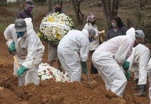 Relatives watch cemetery workers shovel dirt over the coffin of a man who died of Covid-19 (Andre Penner/AP)
