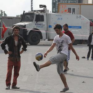 Protesters play football as a police water cannon is parked in the background at Taksim Square in Istanbul, Turkey (AP)