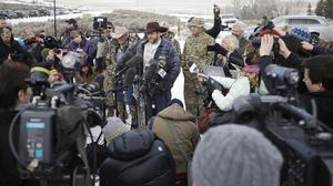 Ammon Bundy, centre, speaks to reporters at Malheur National Wildlife Refuge (AP)