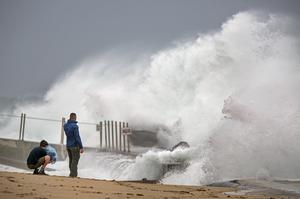 Waves driven by Tropical Storm Isaias crash over the jetty on the north side of the Palm Beach Inlet (Lannis Waters/The Palm Beach Post?AP)
