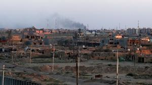 Smoke rises as the sun sets after clashes at the front line in the Qadisiyah neighbourhood in Tikrit (AP)