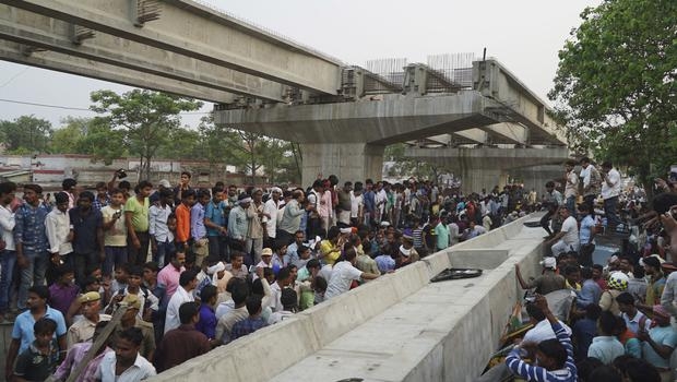 People look for survivors inside vehicles crushed when a section of an overpass collapsed in Varanasi, India (AP)