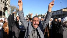 Iraqi Shiite protesters chant slogans against the Saudi government as they hold posters showing Sheikh Nimr al-Nimr, who was executed in Saudi Arabia last week (AP)
