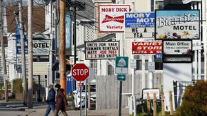 A couple past by a row of closed motels in Maine (Robert F. Bukaty/AP)