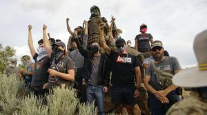 Demonstrators climb the statue of Don Juan de Onate in Old Town in Albuquerque (Adolphe Pierre-Louis/The Albuquerque Journal/AP)
