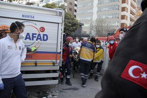 Emergency workers carry a seven-year-old girl rescued from a collapsed building in Izmir to an ambulance (Ismail Gokmen/AP)