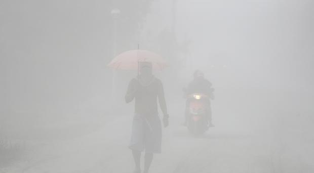 A man walks through a cloud of volcanic ash as he evacuates to safer grounds as Taal volcano erupts (Aaron Favila/AP)