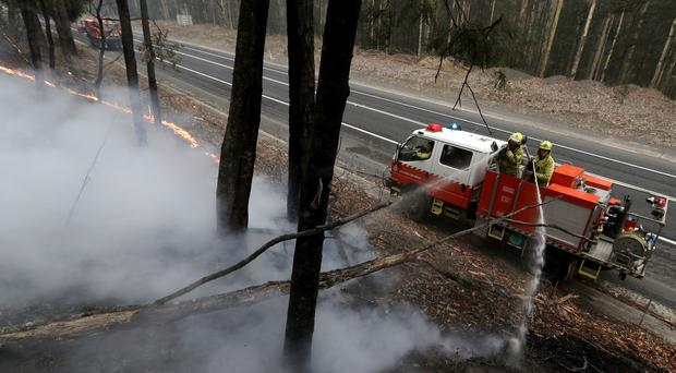 Firefighters manage a controlled burn to help contain a larger fire near Falls Creek, Victoria (Rick Rycroft/AP)