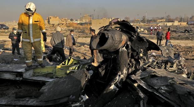 Rescue workers search the scene where a Ukrainian plane crashed in Shahedshahr, south west of the Iranian capital Tehran (Ebrahim Noroozi/AP)