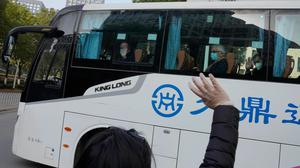 Workers wave to the team of experts from the World Health Organisation (AP Photo/Ng Han Guan)