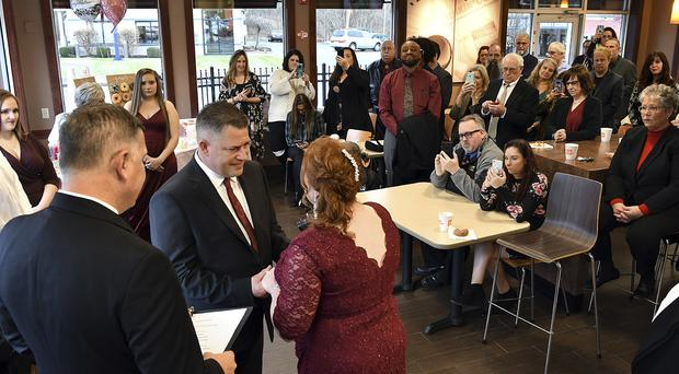 Jason Roy and Valerie Sneade say their vows in front of friends and family at the Dunkin' Donuts in Worcester, Massachusetts (Rick Cinclair/Worcester Telegram and Gazette/AP)