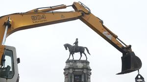 Workers for The Virginia Department of General Services install concrete barriers around the statue of Confederate General Robert E. Lee (Steve Helber/AP)