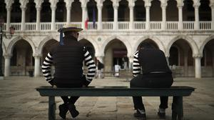 Gondoliers wait for customers in an empty St Mark's square in Venice (Francisco Seco/AP)