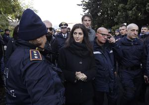 Rome's mayor Virginia Raggi is surrounded by police as she arrives on the scene of a major operation against a prominent criminal family (Gregorio Borgia/AP)